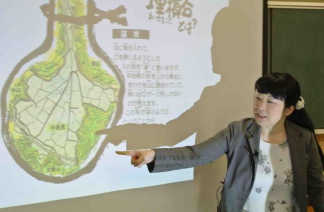 (山に囲まれた袋状の地形について説明する、三井住友信託銀行の石坂彩さん)
